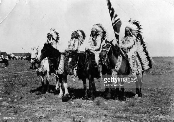 Canadian native chiefs on horseback wearing long feathered headdresses One carries a Union Jack