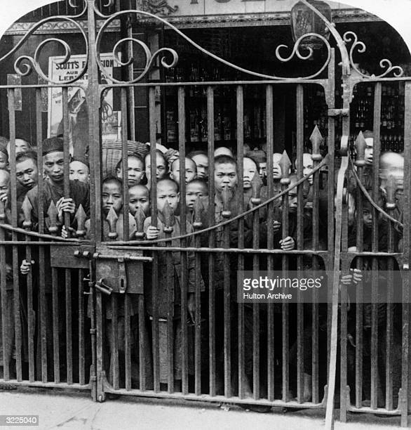 Cantonese boys and men crowd behind the Gate of the English Bridge which barred the Cantonese from the English legations during the Boxer Rebellion...
