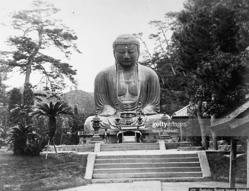 Sitting crosslegged and approached by steps the enormous Sakyamuni Buddha a Daidutsu bronze image at Kamakura