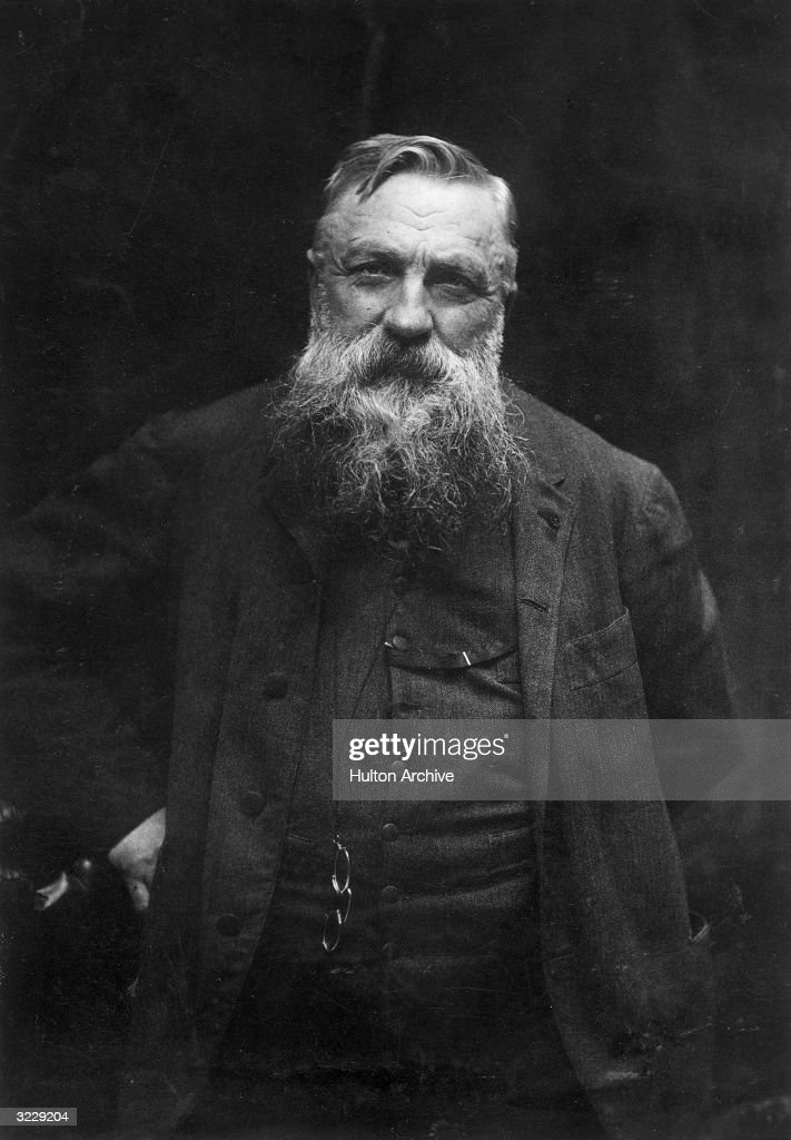 Studio portrait of French artist and sculptor Auguste Rodin standing with his hand on his hip and pincenez eyeglasses hanging from his suit vest