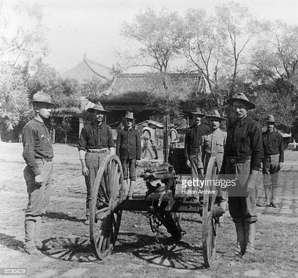 The Ninth US Infantry Gattling Gun Detachment stand around their guns in the Court of the Forbidden City during the Boxer Rebellion Peking China