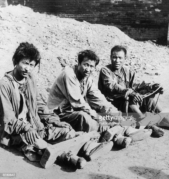 Three captured Chinese Boxer rebels sit with their feet in wooden stocks which are connected by chain links to shackles around their hands and necks...