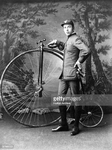A young man standing by the side of his Penny Farthing an early kind of bicycle with a large front wheel and small rear one