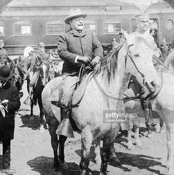 US president Theodore Roosevelt sits atop a horse laughing as he and some other men prepare to enter Yellowstone Wyoming A railroad car sits behind...