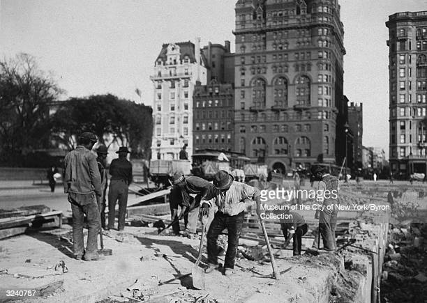 A group of AfricanAmerican workers stand with pickaxes and shovels removing the foundation of the first Plaza Hotel in preparation for the...