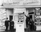 Barkers and ticket takers pose outside the entrance of a nickelodeon theater Signs advertise three shows 'A Laughing Success' 'The Runaway Horse' and...