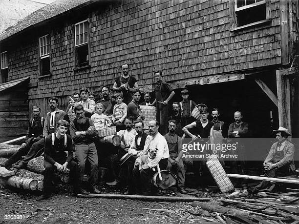 Fulllength portrait of a group of workers standing outside their shingled factory building New England The men and boys sit and stand around a pile...