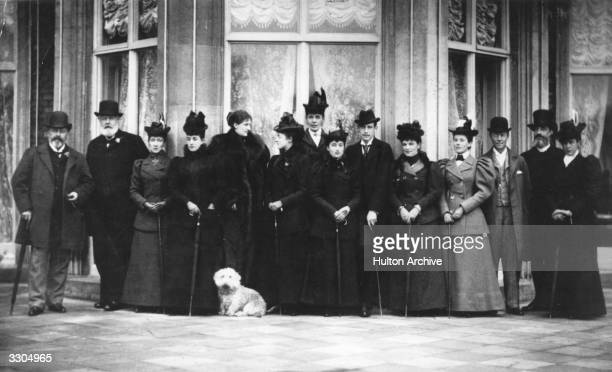Guests at a house party at Sandringham Norfolk Their host British monarch King Edward VII is on the left His favorite dog Caesar is in the foreground
