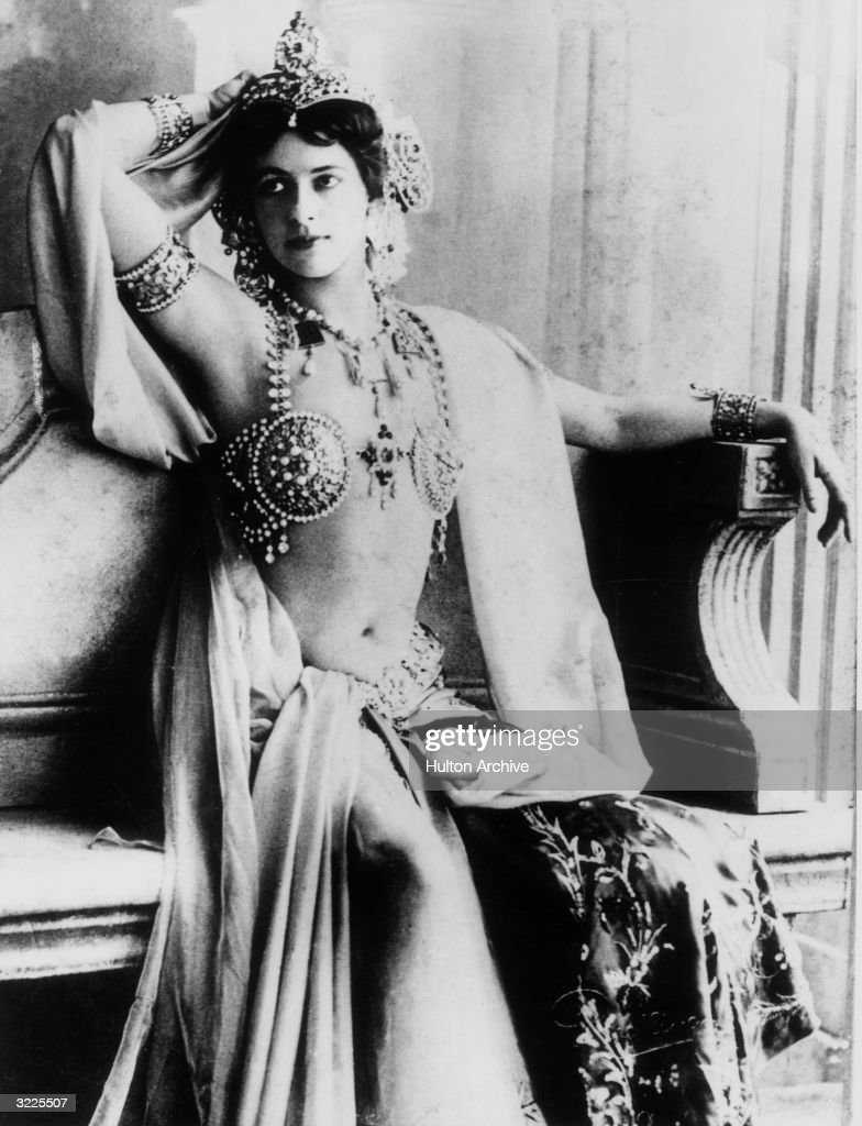 Portrait of Dutch dancer and spy Mata Hari, real name Margarete Geertruida Zelle (1876 - 1917), wearing an exotic jeweled dancing costume with a headdress, bangles, and a brassiere top.