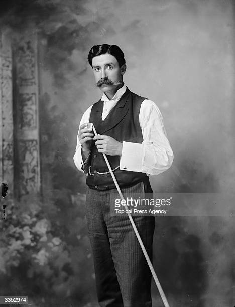 A portrait of Mr Spiller preparing his billiard cue by chalking the tip taken against a painted backdrop