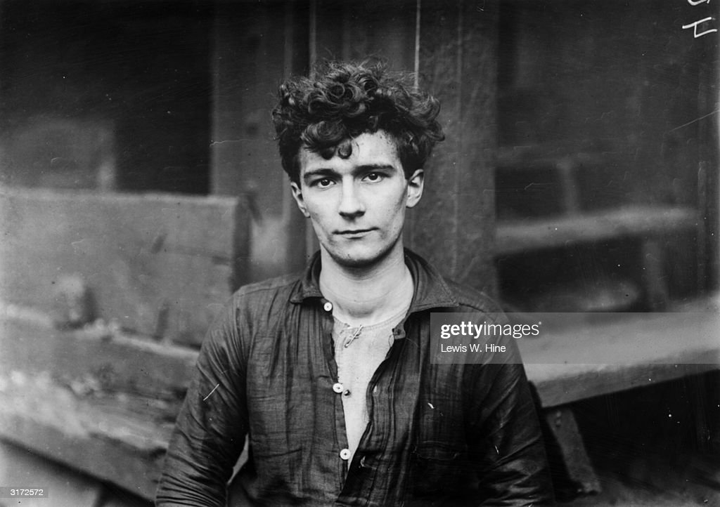 Headshot of a young German steel worker with curly hair. The young man wears a work shirt and underalls.
