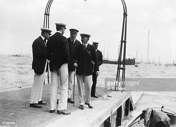 A sailing crew await their departure at the end of the pier