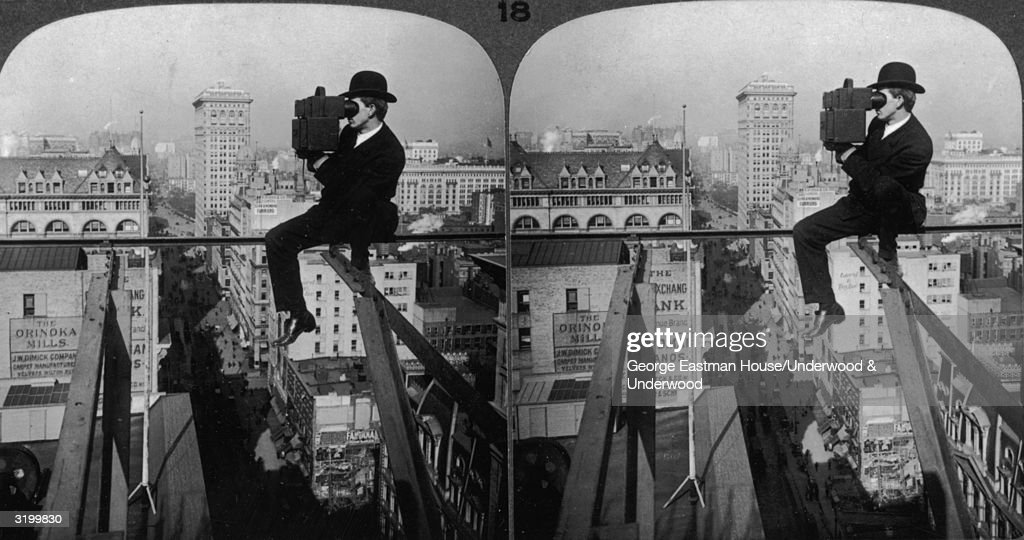 A stereoscope image of a man steadying himself on a thin steel beam suspended high over the streets of Manhattan as he looks up Fifth Avenue, past the Flatiron Building and Madison Square Garden, with his camera, New York City.