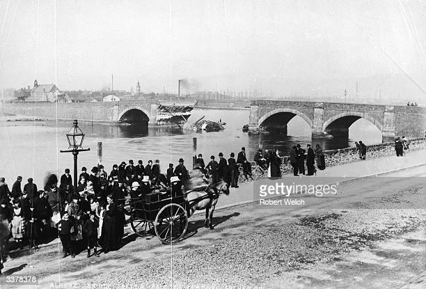 Crowds gathered to look at the gap left by the collapsed central arches of the Albert Bridge at a seaport in Ireland