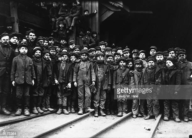 Group portrait of a large number of young male miners wearing their jackets and caps with dirt on their faces Some of the boys perch in the rafters...