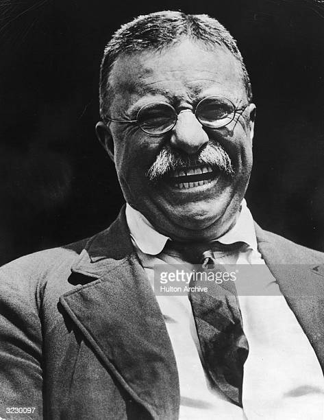 Headshot of American president Theodore Roosevelt laughing in a jacket and tie