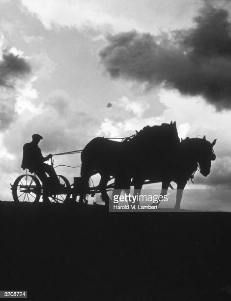 Silhouette of a man plowing a field with two horses