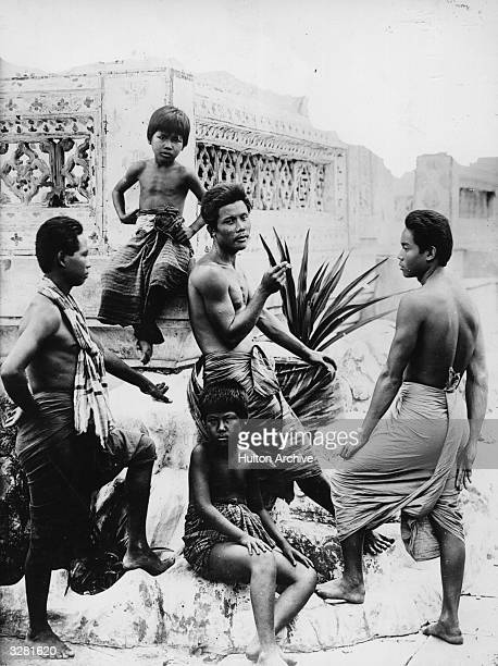 Three men and two boys sporting sarongs relax in Thailand