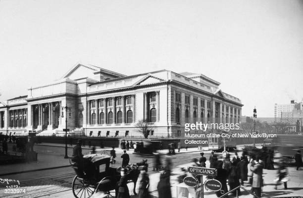 A view of people carriages and streetcars in front of the New York Public Library at Fifth Avenue and 42nd Street New York City The building was...