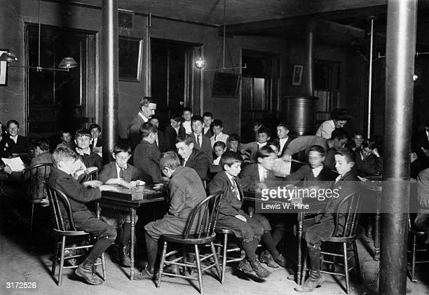 A group of newsboys playing carrom billiard games around tables of four in their workplace reading room Boston Massachusetts c 1912