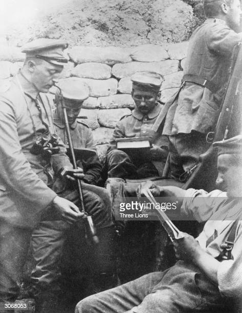 German soldiers in a trench in France during World War I spend a quiet moment reading and writing before the fighting recommences
