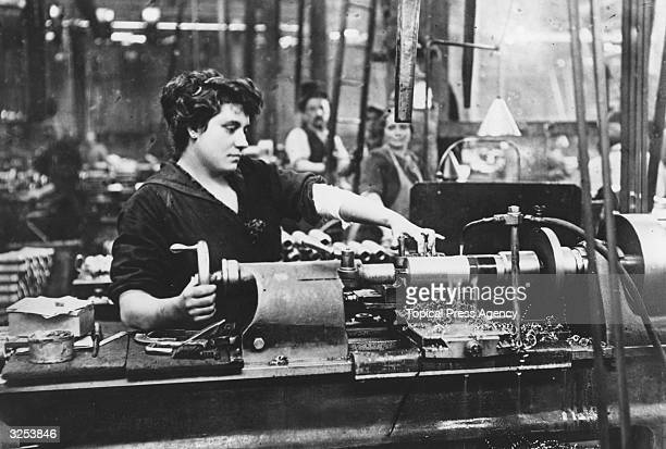 A female worker operating a machine in an armaments factory