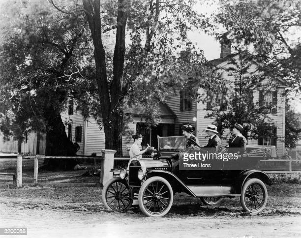 A group of friends in their Model T Ford car collecting something from a woman at a farm perhaps water to cool the engine
