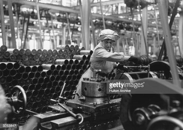 A woman munitions worker operating a machine in an armaments factory during the First World War