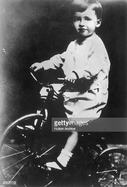 Full length studio portrait of American actor James Stewart as a child posed on a tricycle