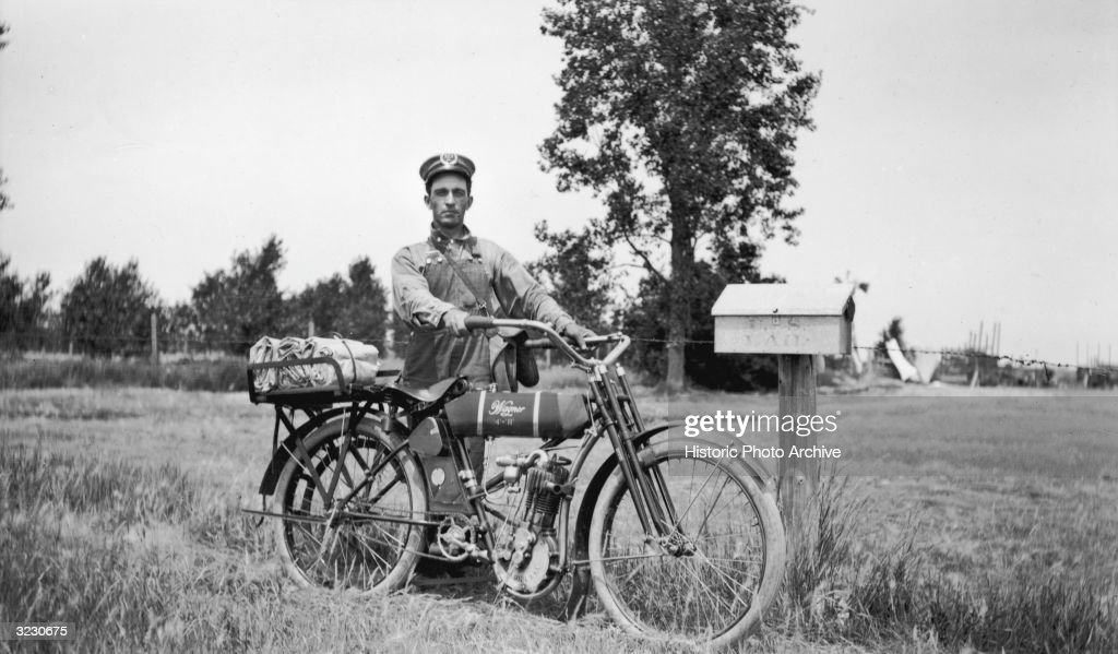 Outdoor portrait of a rural postal mail carrier, standing with his Wagner 4-11 motorcycle next to a postal box on his route near Newell, South Dakota. He wears a cap and overalls, with sacks of mail in a basket on the rear of his motorcycle.