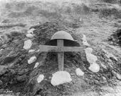 A helmet hangs on a makeshift wooden cross on the dirt grave of an unknown Canadian soldier World War I