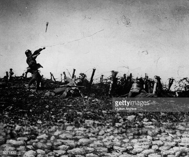In the course of an attack on an Allied trench two Germans drop behind cover whilst a third hurls a hand grenade