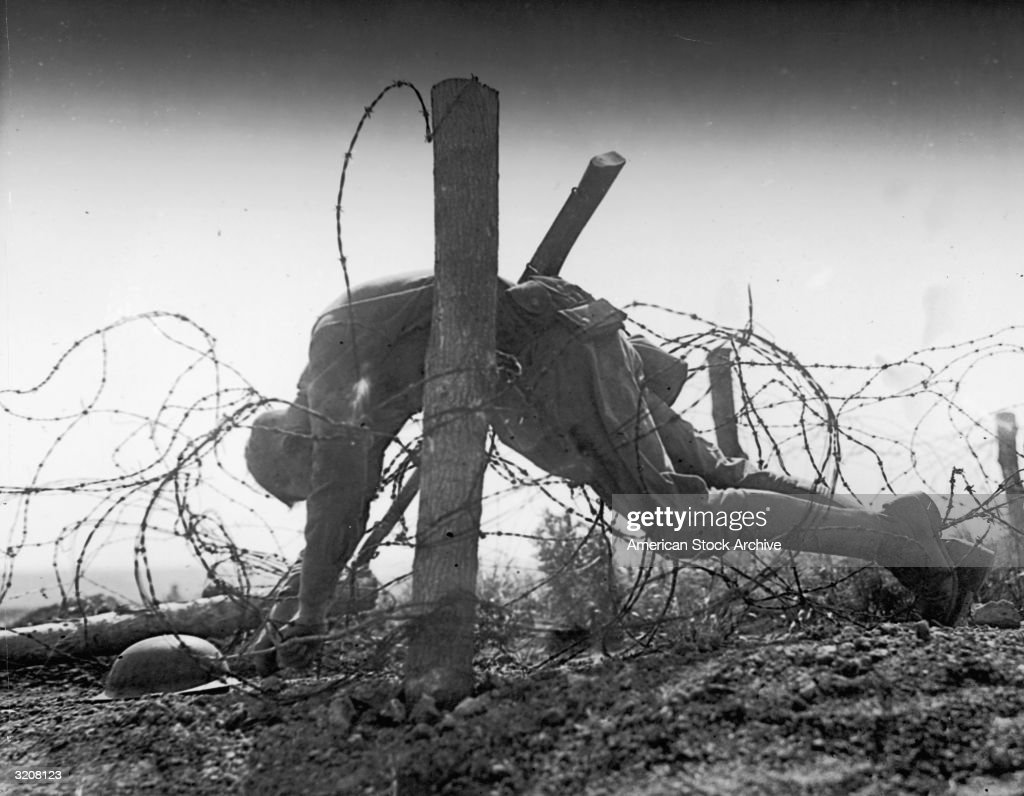 An American soldier lies dead tangled in the barbed wire Northern Europe WWI
