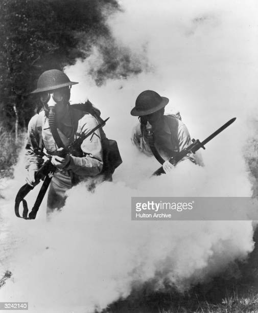 Two US soldiers wear gas masks while walking through plumes of smoke during World War I
