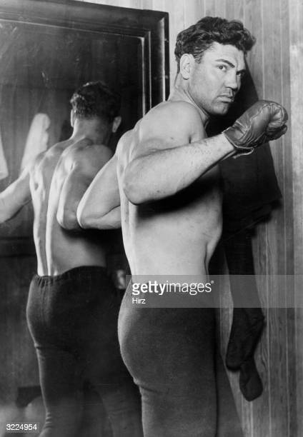 American heavyweight boxing champion Jack Dempsey wearing boxing gloves and tights poses in fighting stance next to a mirror