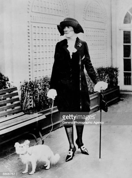 A woman wearing a suit comprising a jacket and knickerbockers with laceruffled blouse and buckled highheeled shoes
