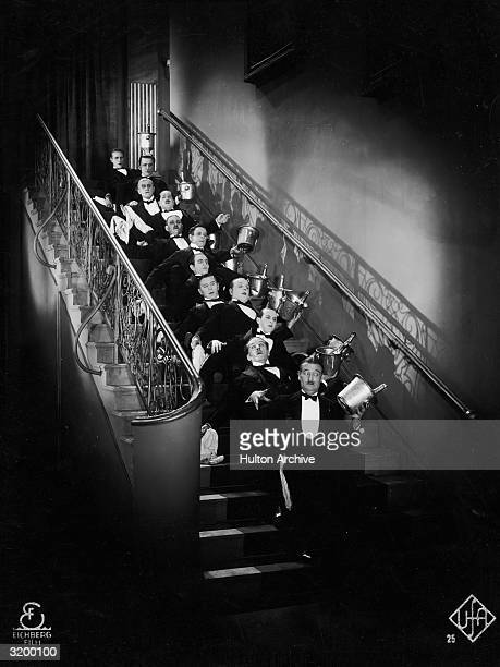 A line of waiters carrying bottles of champagne in coolers fall up a flight of stairs