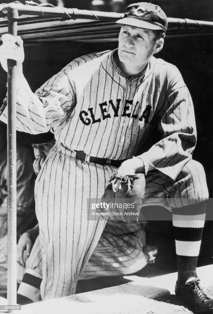 A portrait of baseball pitcher Walter Johnson wearing a Cleveland uniform and a baseball glove leans on his knee while gripping a bar inside a dugout