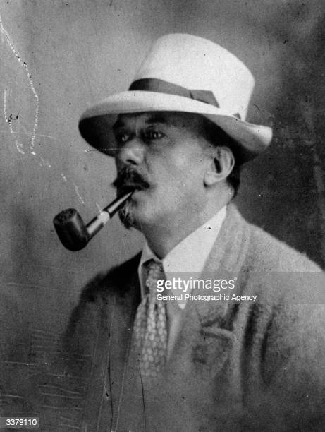 English author occultist magician and mountaineer Aleister Crowley smoking a pipe