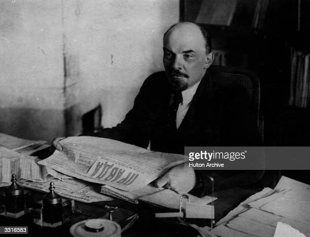 Russian revolutionary and communist leader Vladimir Ilyich Lenin reading a copy of Russian newspaper 'Pravda'