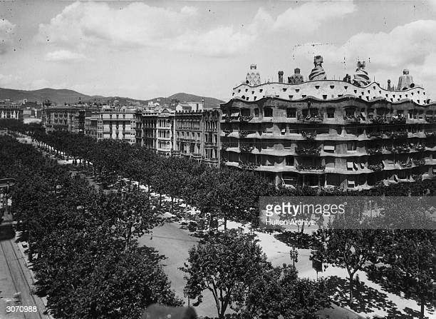 The tree lined Paseo de Gracia in Barcelona The corner apartment building with highly decorated chimney pots is the 'Casa Mila' by Antonio Gaudi...