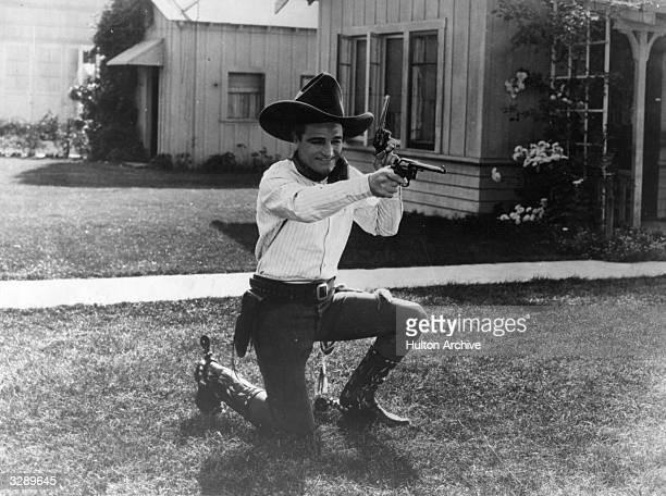 Tom Mix the famous silent era cowboy star booted and spurred and in action with a brace of pistols on someone's front lawn