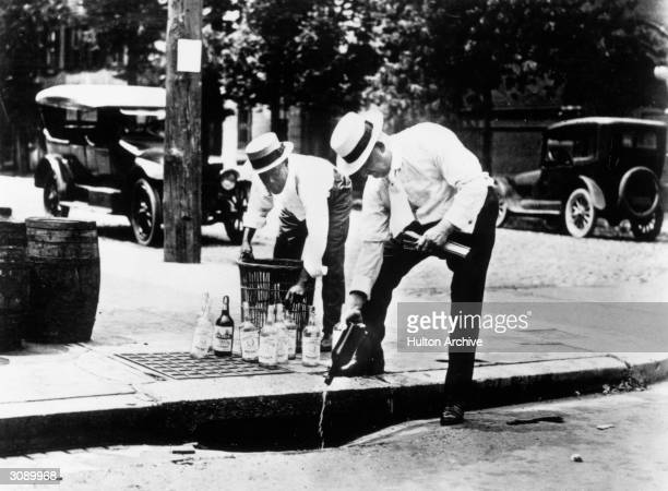 Two men pouring alcohol down a drain during prohibition in America
