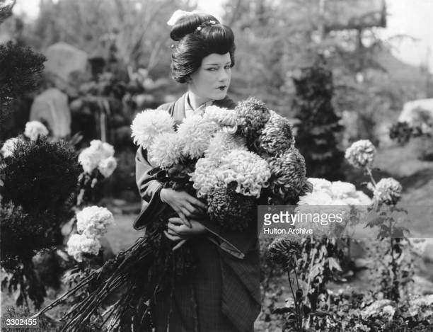 Viola Dana appears in Japanese clothing carrying armfuls of chrysanthemums in a scene from the film 'Willow Tree'