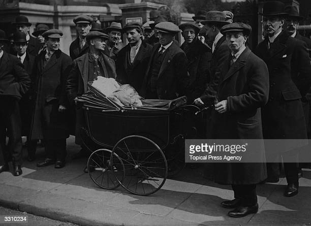 A group of striking miners with a baby sleeping in a pram