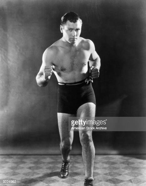 Fulllength studio portrait of American heavyweight boxing champion Jack Dempsey clenching his fists in a fighting stance