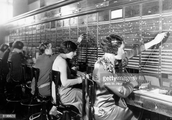 A line of female telephone operators sit at a large switchboard connecting calls at the Central Phone Exchange