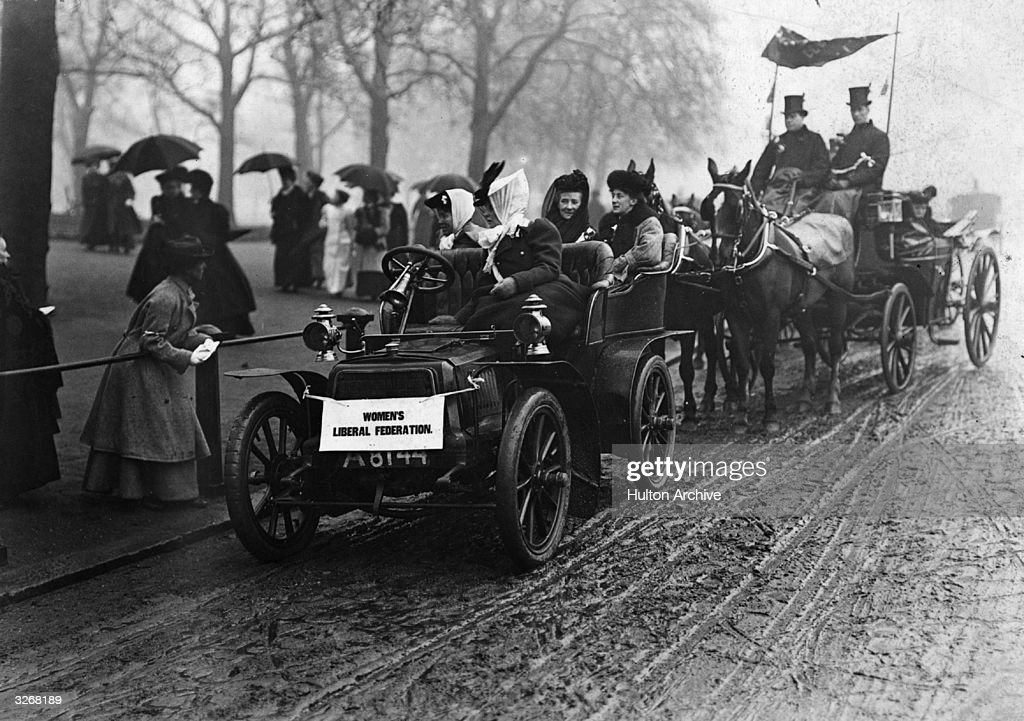 Four members of the Women's Suffrage Movement in a car at a demonstration.