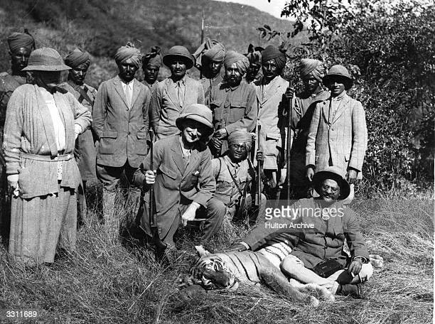 A dead tiger at the feet of Lord Reading Viceroy of India with the Maharaja of Gwalior and beaters after a tiger shoot in Gwalior State