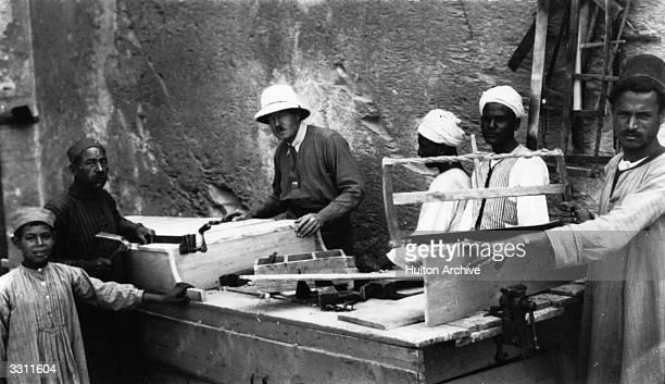 English egyptologist Howard Carter supervising carpenters preparing to reseal Tutankhamen's tomb